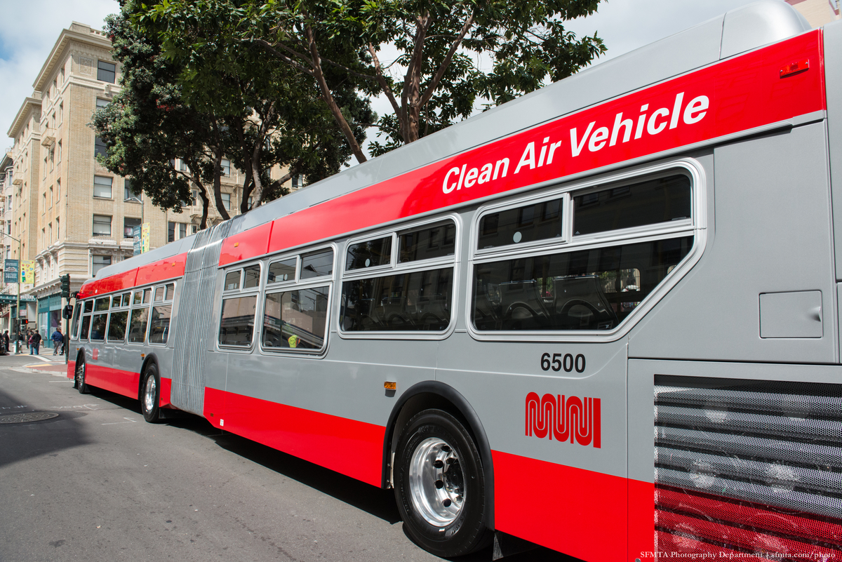 """A new, long Muni bus stopped at a street curb. The words """"Clean Air Vehicle"""" are painted on the side."""