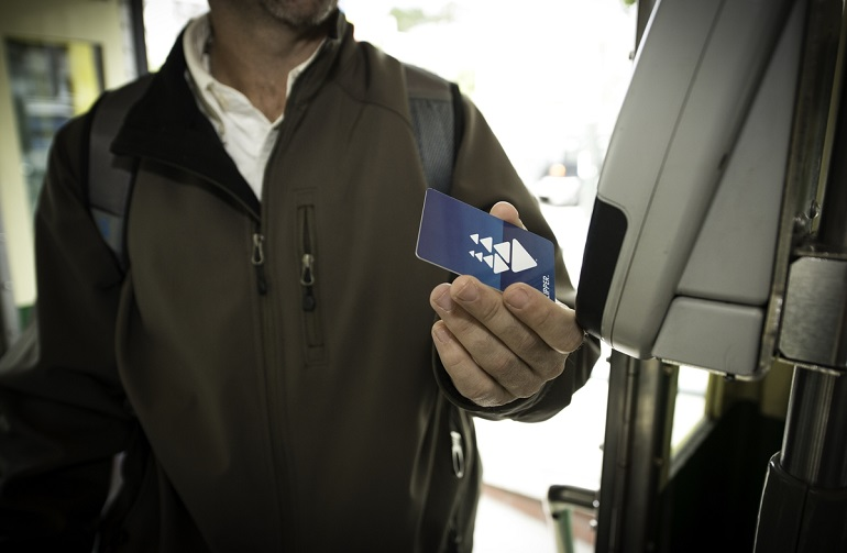 A man entering a Muni vehicle holds a Clipper Card in front of a digital card reader.