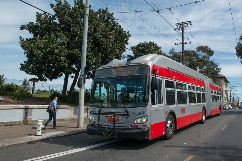 "A new 60-foot Muni bus sits curbside with a digital headsign displaying the text, ""Bus in test - no passengers."" A man on the sidewalk looks at the bus as he walks by."""