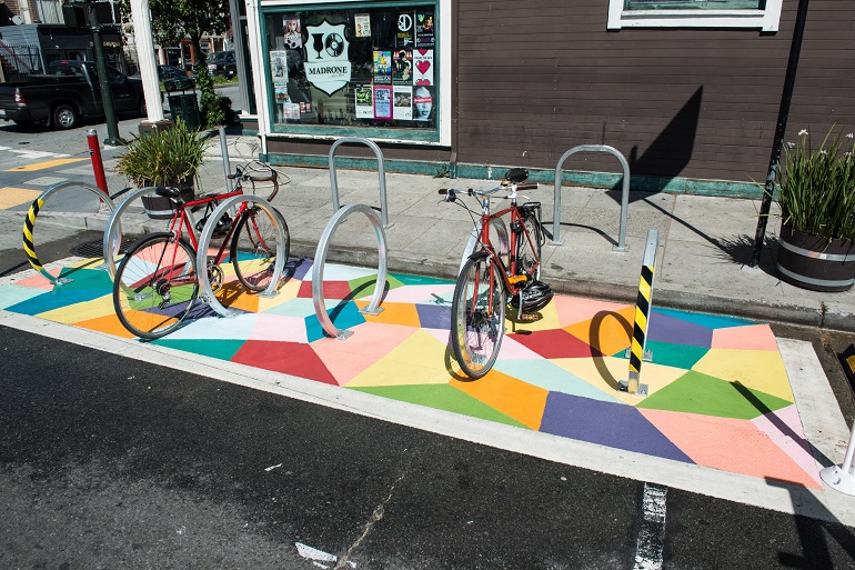 A curbside area, about the size of a car parking space, features six bicycle racks and pavement painted with a colorful mural of shapes.