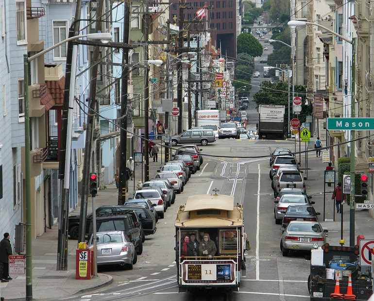 A downhill view of Washington Street at Mason Street. A crowded cable car travels down the street between two rows of parked cars as cars and delivery trucks travel by in the background.