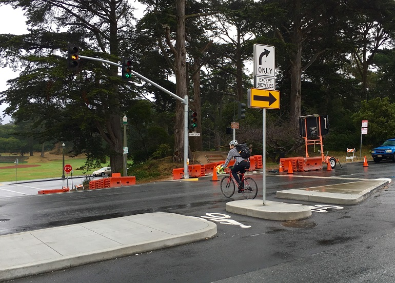 Just outside of Golden Gate Park, a man bikes through an opening in a traffic island in the middle of an intersection. The island features two openings marked for bicycles to pass through, and a traffic signal with a bicycle symbol is overhead.]