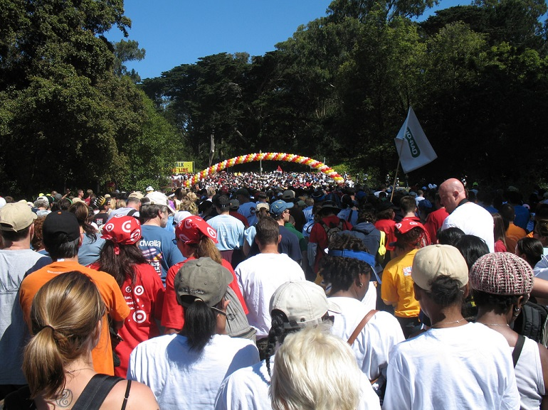 Thousands of people together in the park surrounded by trees under a bright blue sky.