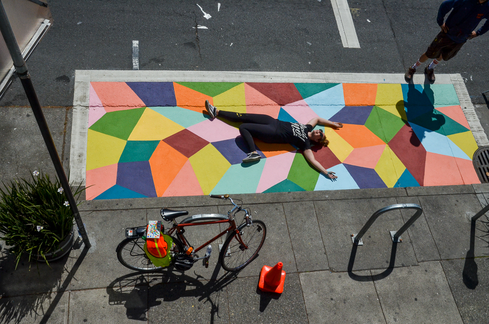 Artist Kristin Farr lays in her new mural on curbside pavement.