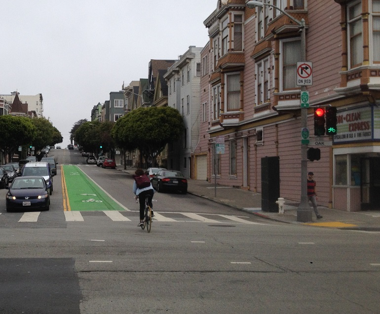 A bicycle rider crosses Oak at Scott Street towards a green left-turn bike lane while. A bicycle signal shows green while a vehicle traffic signal shows red.