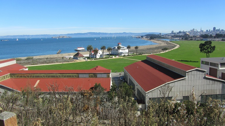A panoramic view of Chrissy Field under a bright blu sky with blue bay water in the background.