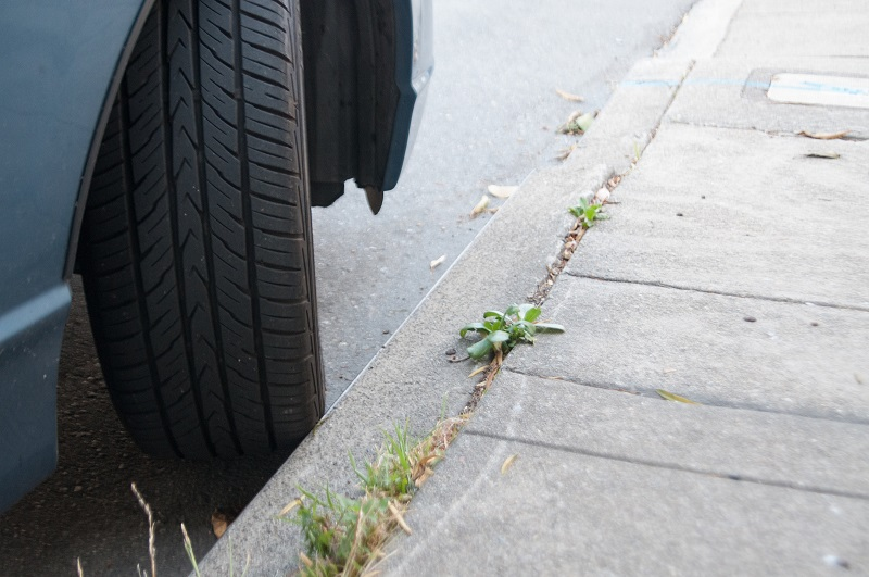 A car parked with its front wheel turned to touch the curb.