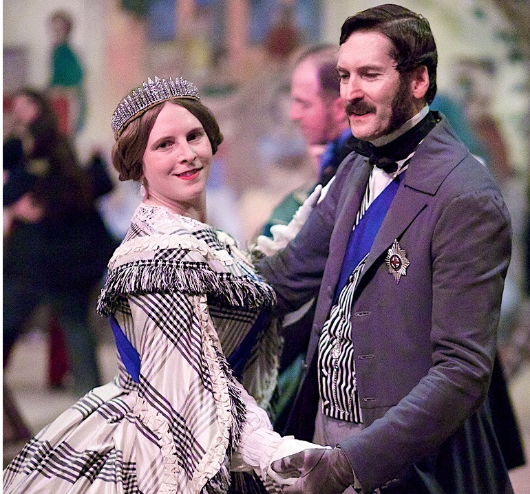 A couple in Victorian-era clothing dancing together.