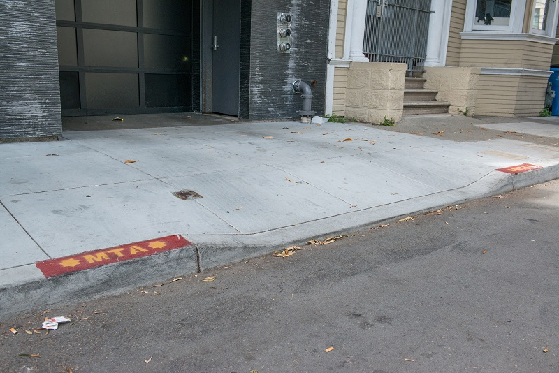 "A driveway with short red curb zones on either side and an ""MTA"" stencil marking."