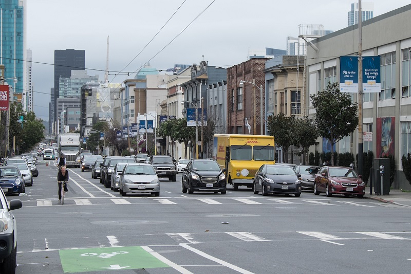 Folsom Street with car traffic and bicycle riders in a bike lane.