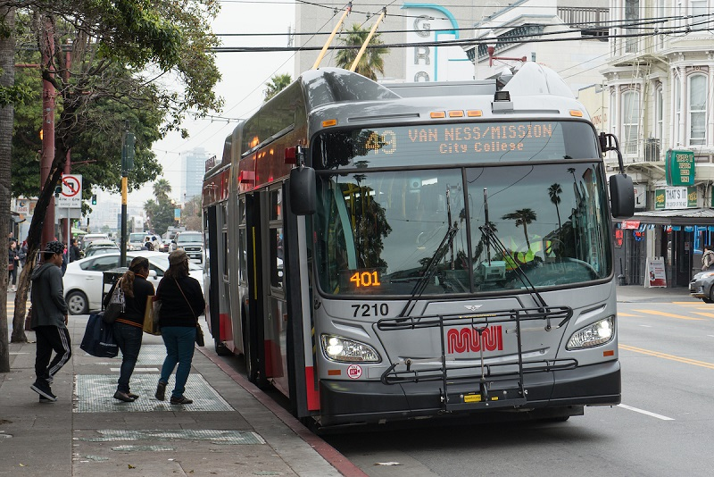 A Muni trolley bus at a curbside stop with customers boarding.