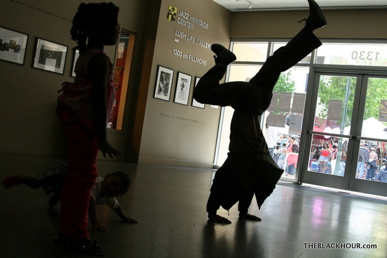 silhouette of a dancer doing a handstand watched by children in a lobby