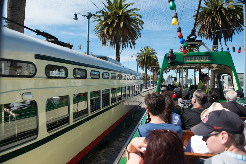 People ride a historic tram car past a streetcar on The Embarcadero.