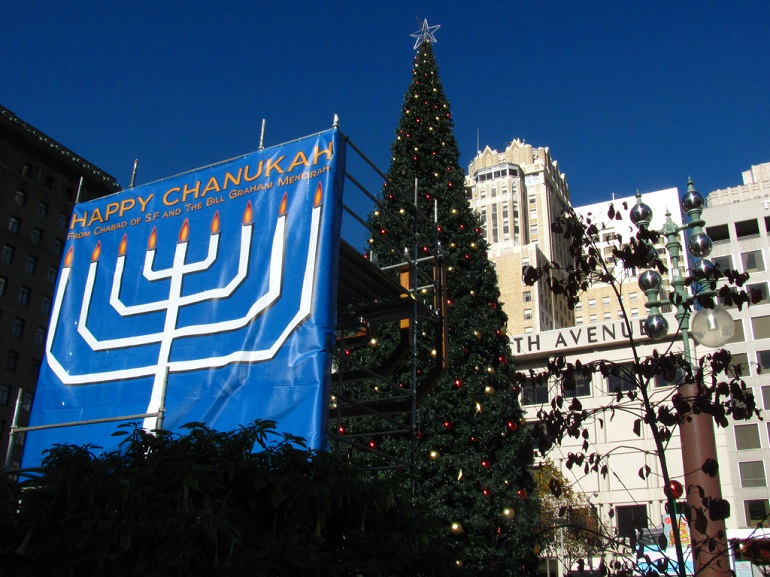 Menorah and Christmas tree in Union Square on a bright blue afternoon.