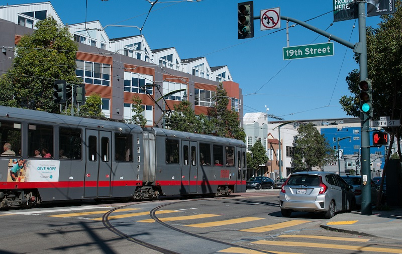 A Muni train on the T Third Line travels down Third Street next to a track spur that turns down 19th Street.