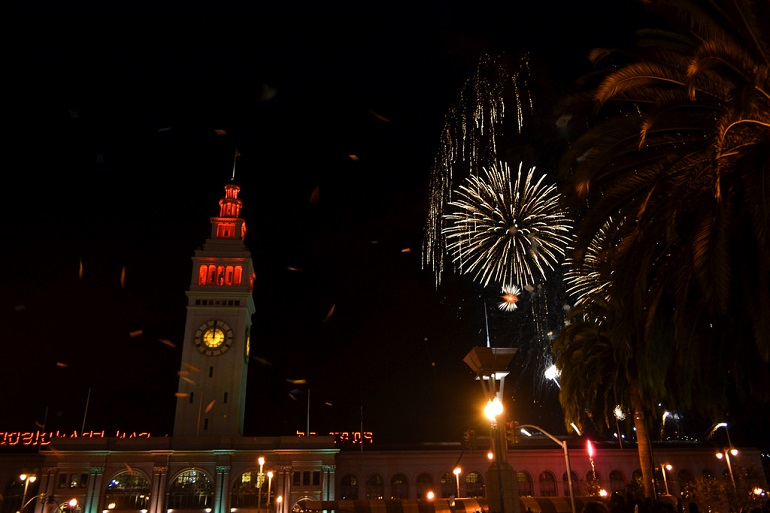 Ferry Building under a dark night sky with fireworks going off.