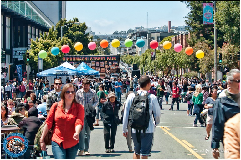 People out enjoying a street fair under a bright afternoon sky.