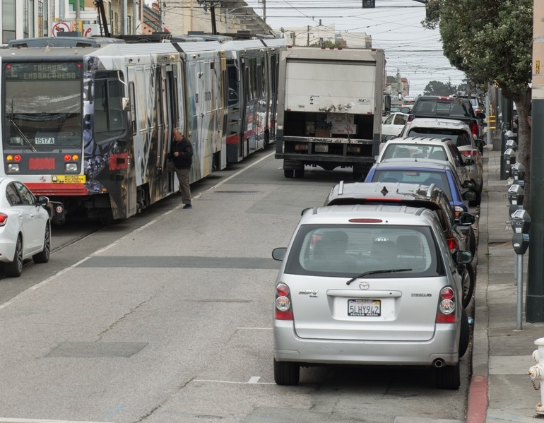Parked cars sit along the curb on Taraval Street as a man boards a Muni L Taraval train in the roadway.]