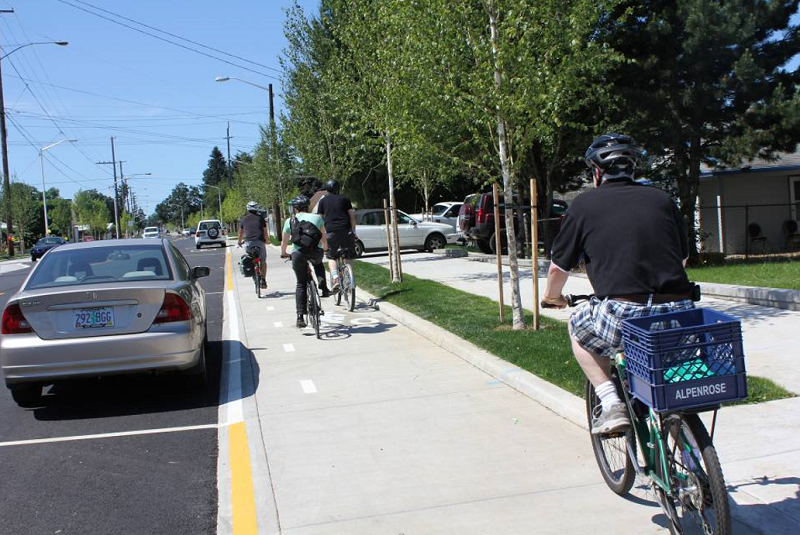 People bike on a raised, parking-protected bike lane in Portland, Oregon.