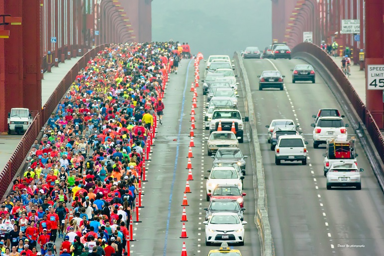 Thousands of runners in colorful atttire run across one side of the Golden Gate on an overcast morning.