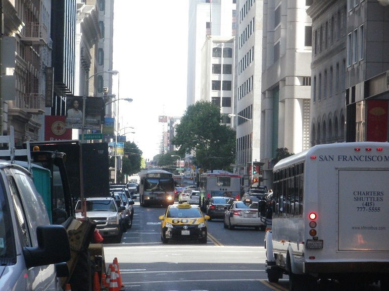 A view of Sansome Street in the Financial District. The single southbound traffic lane is used by a Muni bus and taxi, while several lanes in the opposite direction are used by  cars, buses and a shuttle van.