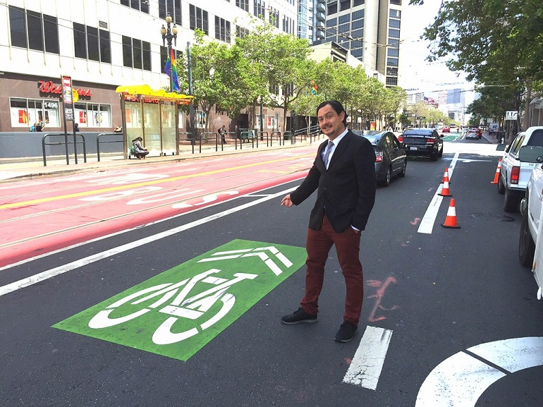 "SFMTA planner Oliver Gajda stands on Market Street pointing to a bike ""sharrow"" marking on the roadway."