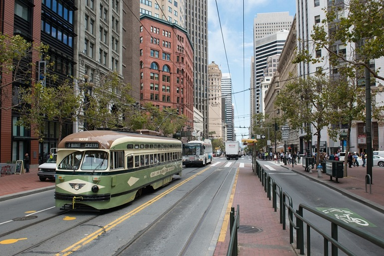 A Muni historic streetcar, trolley bus and other vehicles travel on Market Street at 3rd Street.