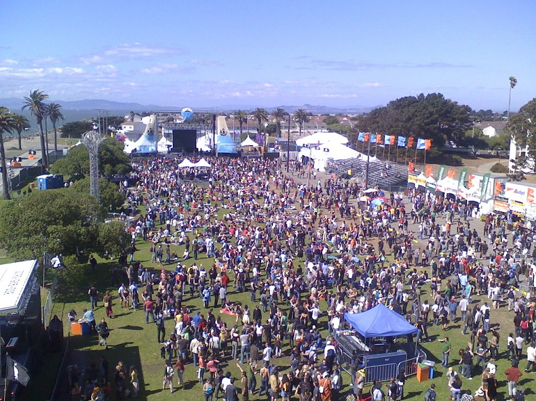 Aerial view of large crowd of people gathered on Treasure Island for a music concert during a sunny afternoon.
