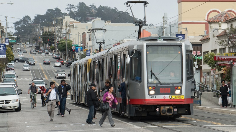 People in the roadway on Taraval Street board and alight from a stopped Muni train.