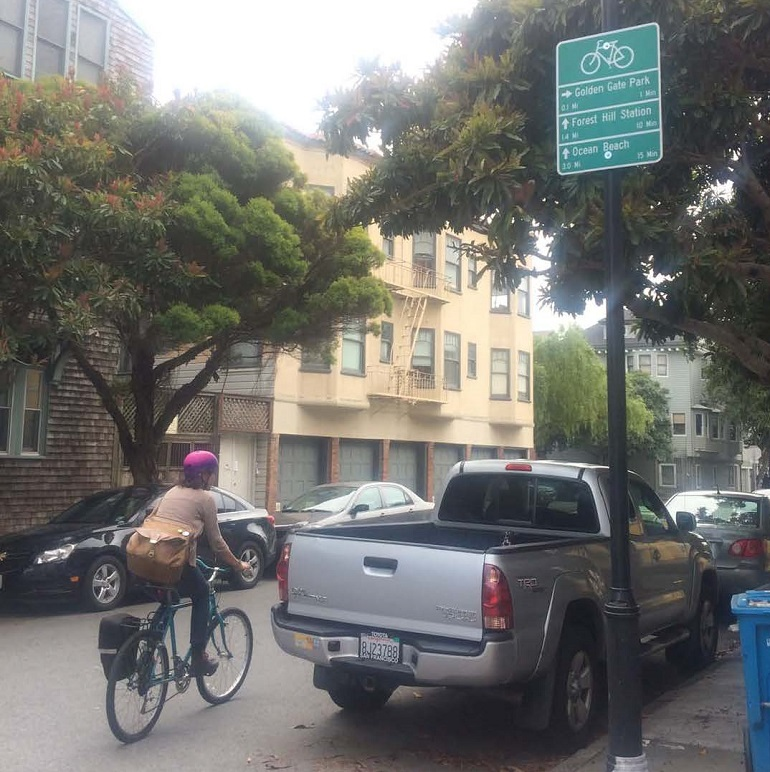 A woman bikes down a street past a bike wayfinding sign posted on a street light pole.