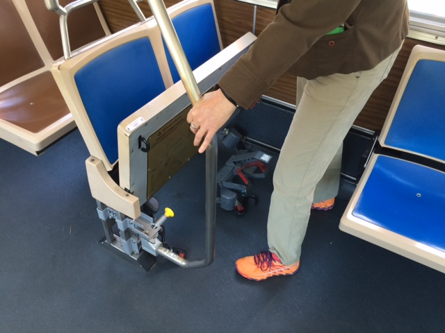 Woman holding the rotational stanchion, which is turned outwards to allow room for the seats to flip down.