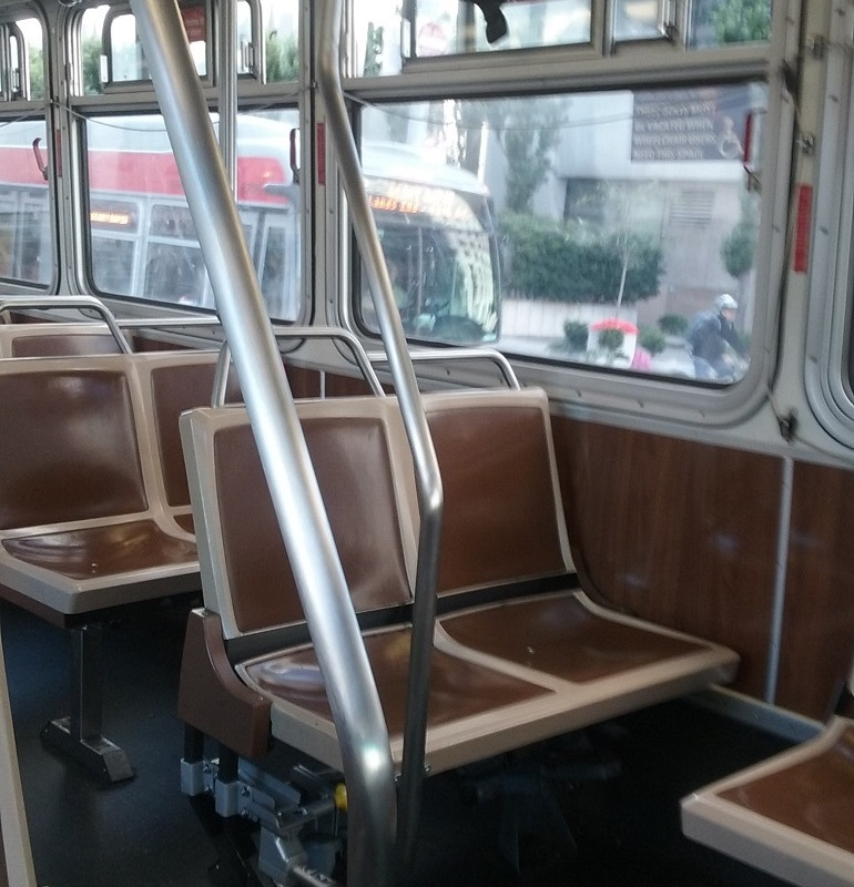 A view of the inside of a Muni bus with front forward-facing seats folded down and newly-installed curved metal poles.