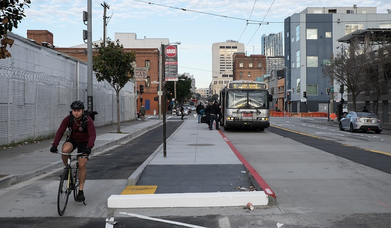 A man rides in a bike lane between the sidewalk and a concrete island where people board a Muni bus on 11th Street at Harrison Street.