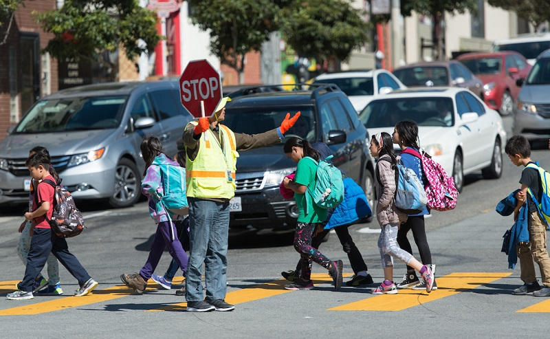 A crossing guard holds a stop sign as children walk in a crosswalk in front of stopped cars.