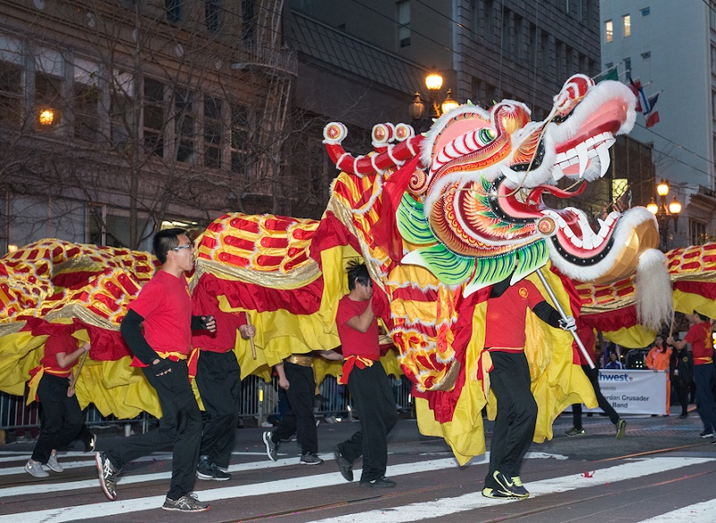 A brightly colored dragon is carried through the parade route.