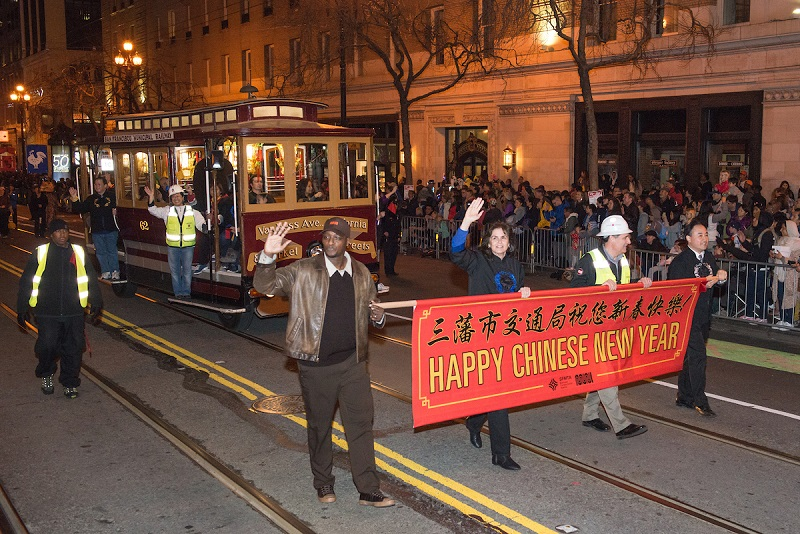 "Motorized cable cars glowing with Chinese lanterns is led down Market Street by SFMTA staff carrying a ""Happy New Year"" banner."
