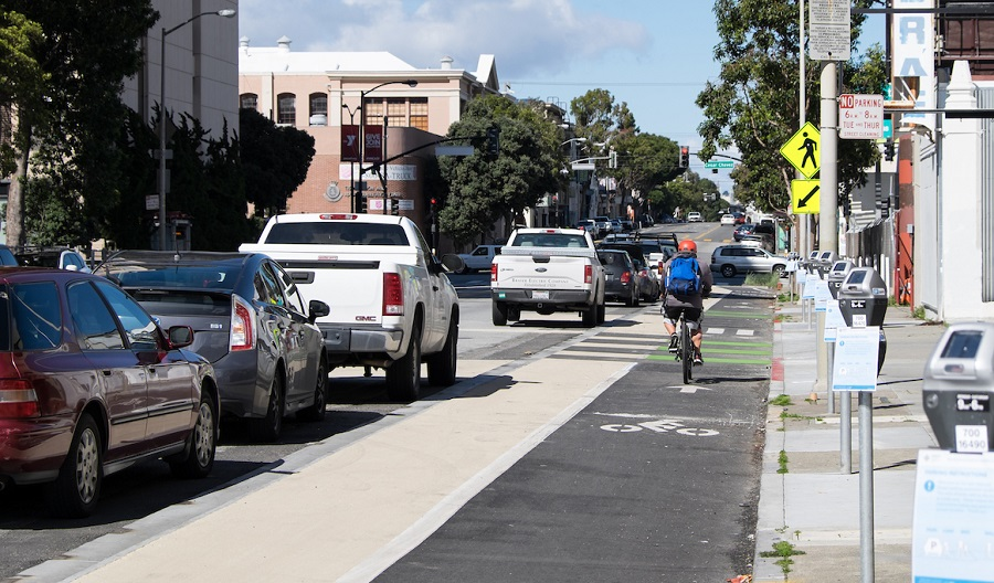 A person bikes in a bike lane on Valencia Street between a lane of parked cars and a sidewalk curb.