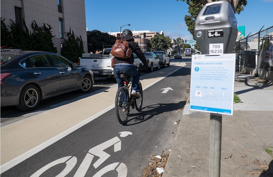 A person bikes on Valencia Street in a bike lane placed between a lane of parked cars and a sidewalk curb, with parking meters featuring instructional flyers.