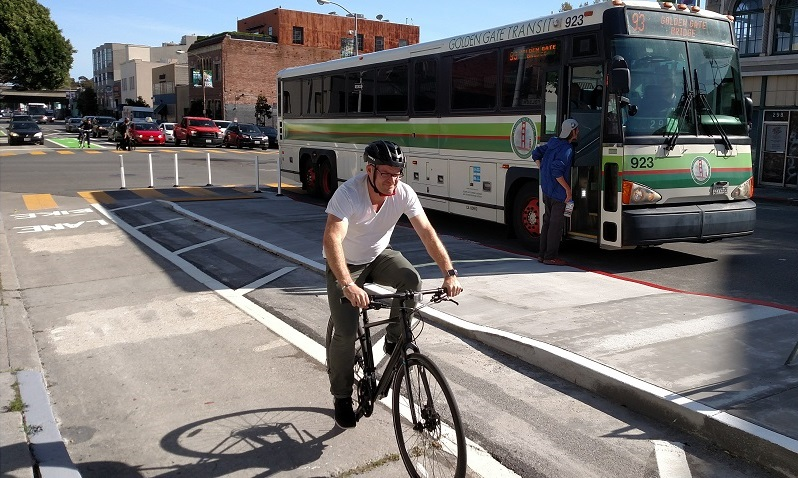 Man biking in a parking-protected bike lane and transit boarding island on 7th Street.