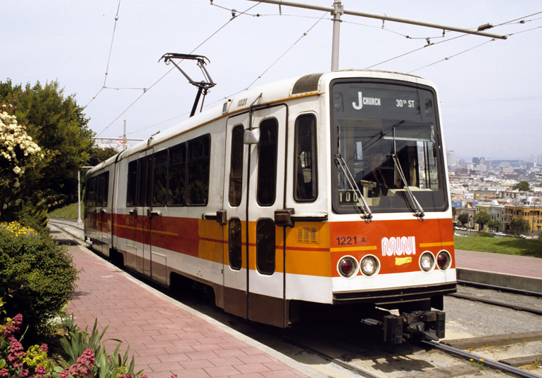 color photograph showing a Muni Boeing LRV climbing the hill in dolores park in the 1980s.  The car is stopped near the top of the hill with a view of the city skyline behind it.