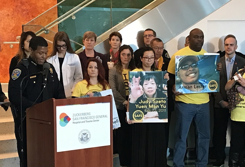 San Francisco Police Chief William Scott speaks at a podium. Behind him are city officials and safe streets advocates wearing yellow shirts and holding large photos of traffic collision victims.