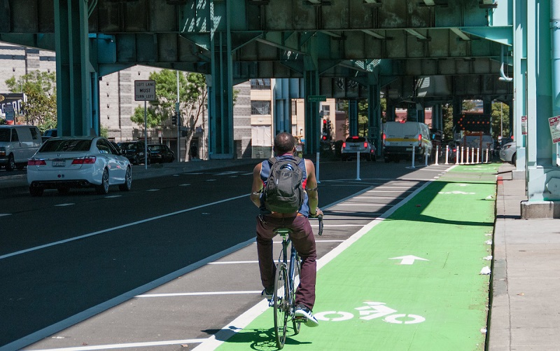 A man bikes in 13th Street's new parking-protected bike lane.