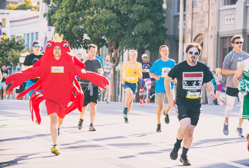 Men running in the Bay to Breakers race, including one wearing a lobster costume.