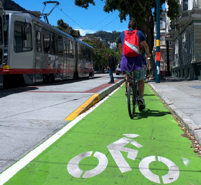 A man rides a bike in a bike lane that runs between the curbs of a sidewalk and transit boarding island next to a Muni train at Duboce Avenue and Church Street.
