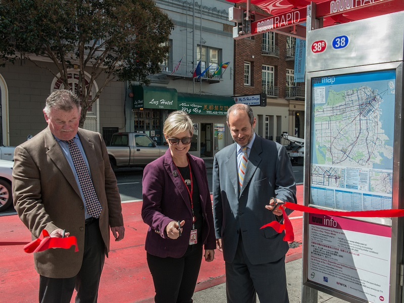 Two men and a woman hold scissors to cut a red ribbon while standing next to a new transit shelter with a red awning and a red traffic lane behind them.