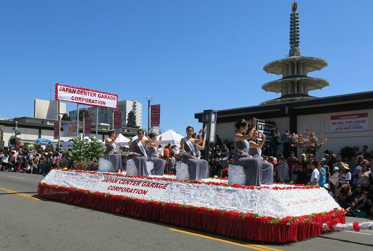 Ladies in gray dresses sit on a red and white float waving to the crowd under a bright blue sky.