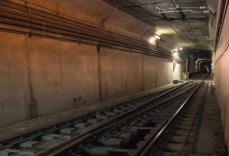 A junction of joining rail tracks inside the Muni subway tunnel.