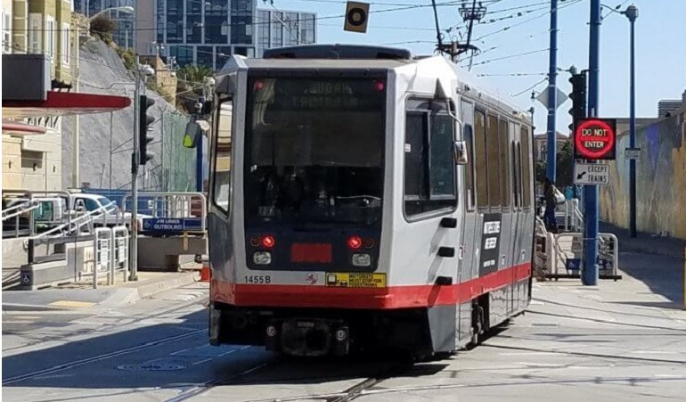 An N Judah Muni Metro train enters the subway portal at Duboce Avenue and Church Street.
