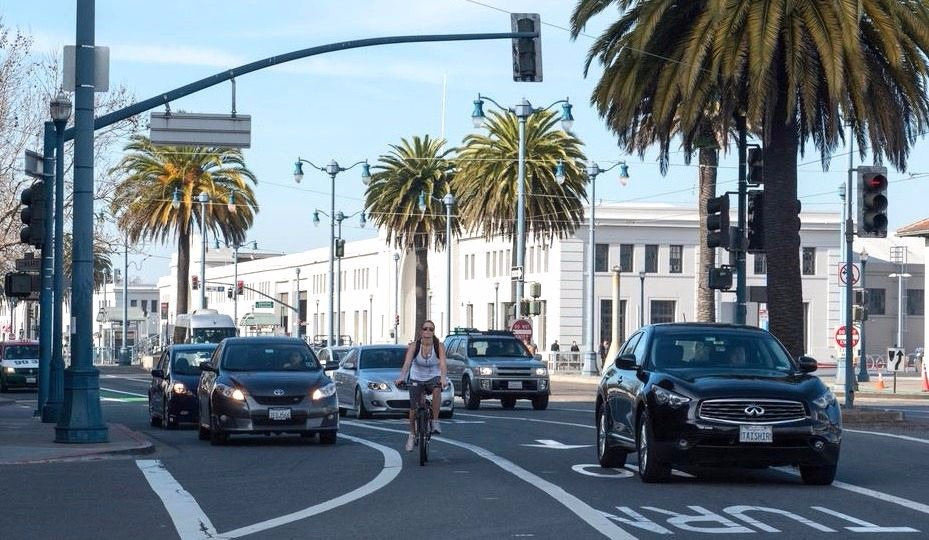 A woman rides in a narrow bike lane across an intersection on The Embarcadero between lanes of car traffic.