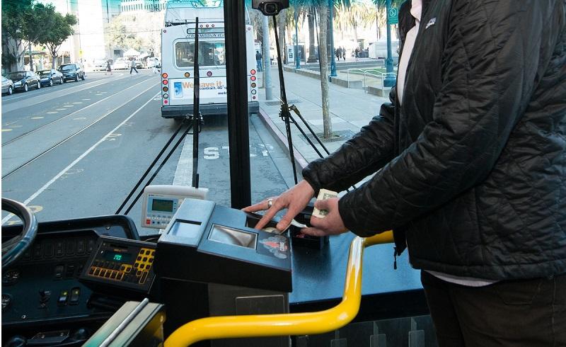 Man on a Muni bus feeding cash bills into a farebox.